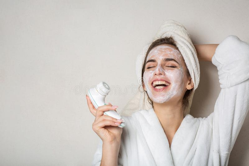 Laughing brunette girl posing with moisturizing cream mask and face cleaner. Empty space. Laughing brunette woman posing with moisturizing cream mask and face royalty free stock image
