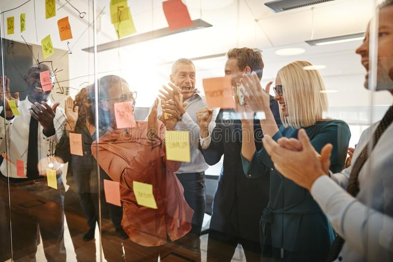Laughing businesspeople clapping after an office brainstorming s royalty free stock photo