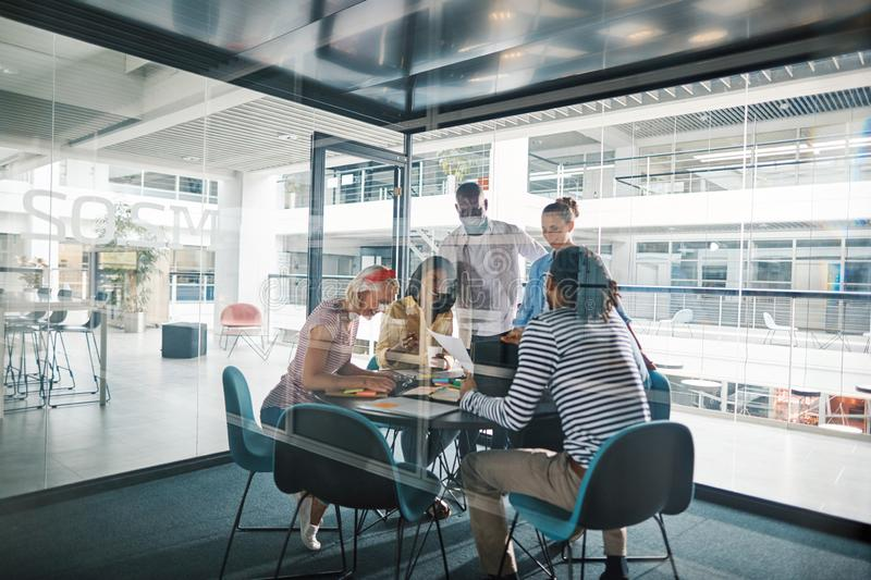 Laughing businesspeople working in a glass walled office boardro stock photo