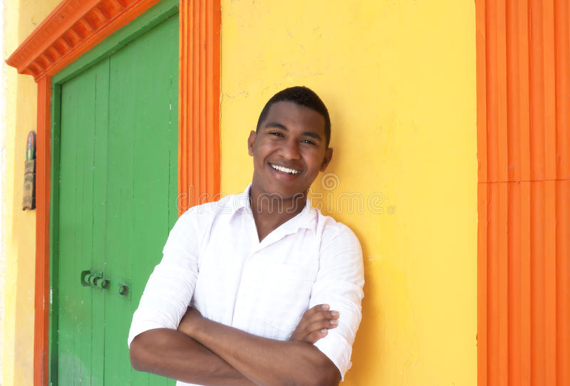 Laughing caribbean guy in front of a colorful house royalty free stock photo