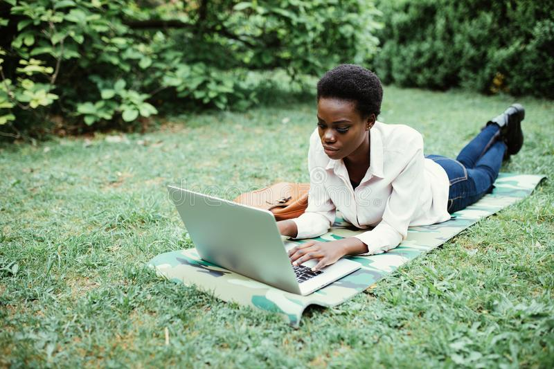 Calm to work outdoors. Young afro american student lying on grass taking notes on campus at college royalty free stock image