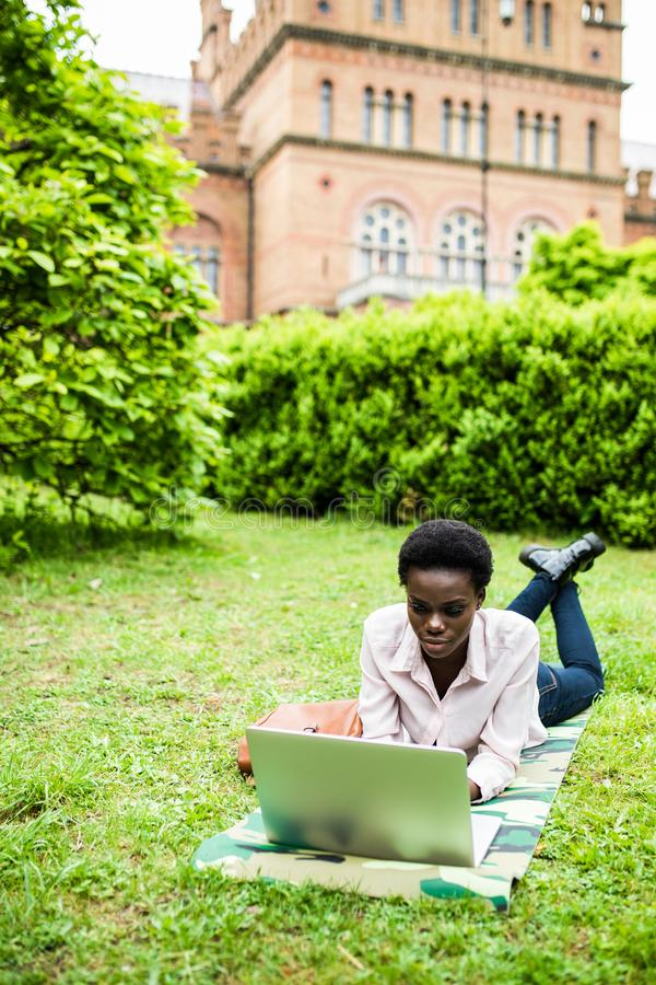 Surf in internet. Young afro american student lying on grass taking notes on campus at college stock photography