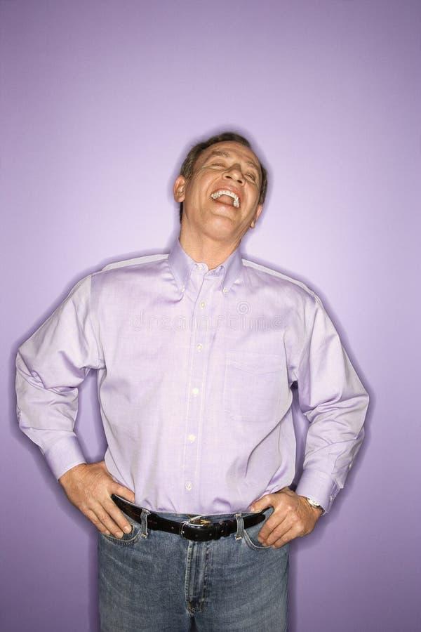Laughing Caucasian man wearing purple clothing.
