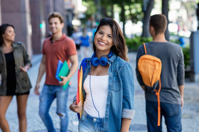 Laughing caucasian young adult woman walking in city with group of students royalty free stock photos