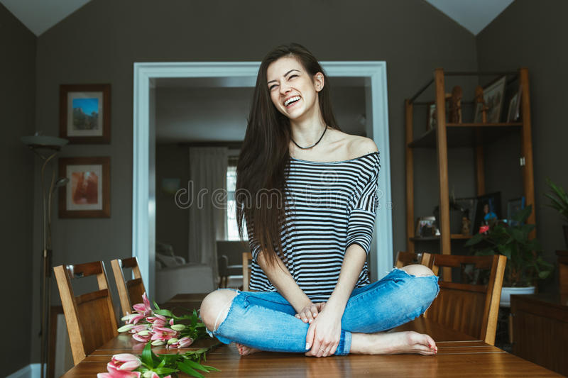 Laughing Caucasian young beautiful woman model with messy long hair in ripped blue jeans and striped t-shirt sitting on table. Portrait of smiling laughing royalty free stock photography