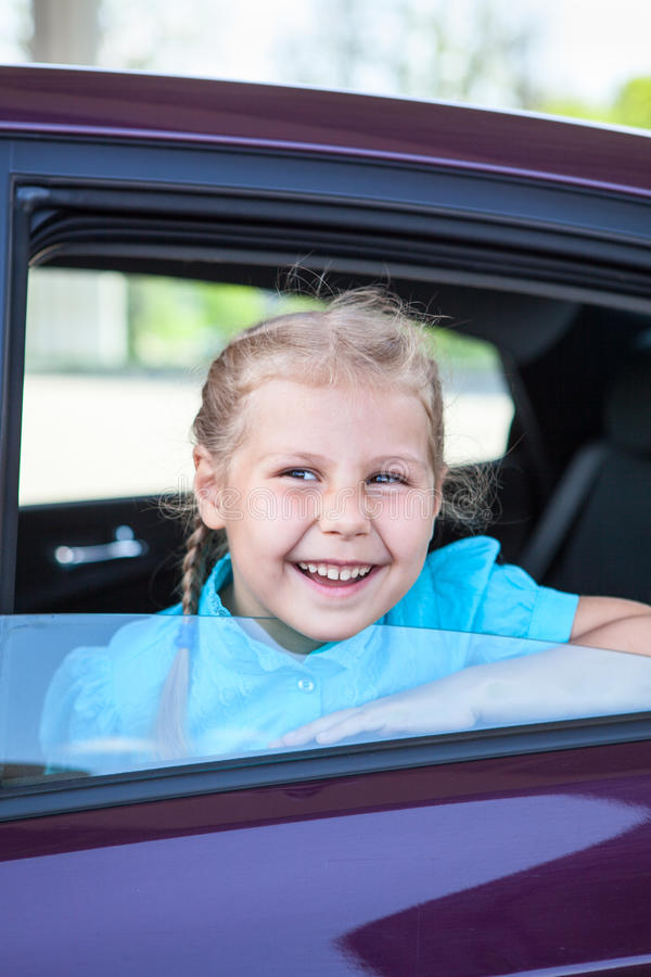 Laughing child looking through car side window sitting in safety seat royalty free stock image