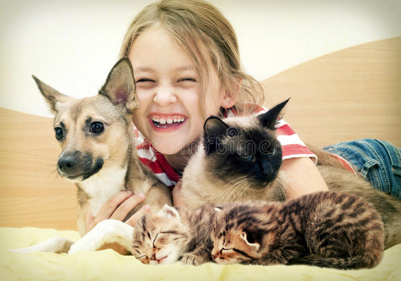 Laughing child and pets royalty free stock photography