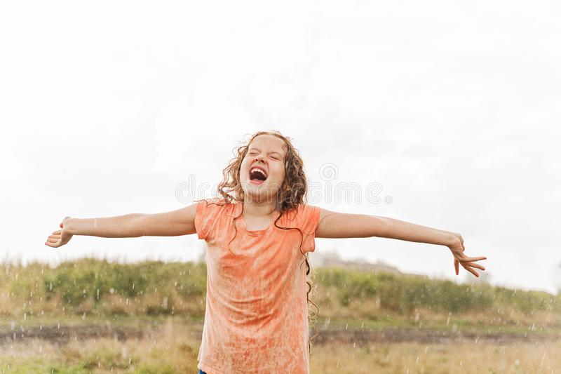 Laughing child spread its arms and catches raindrops royalty free stock images