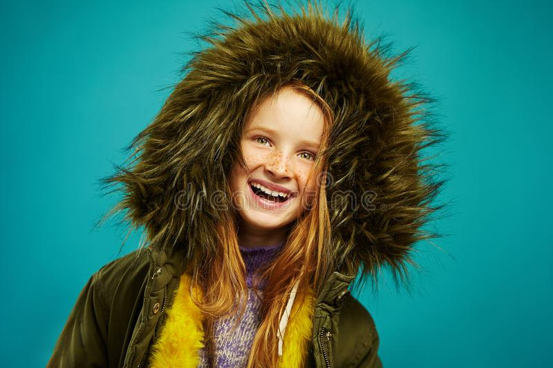 Laughing children girl with red hair and beautiful freckles wears warm autumn hooded jacket on blue solid background. Happy child in winter clothes stock photo