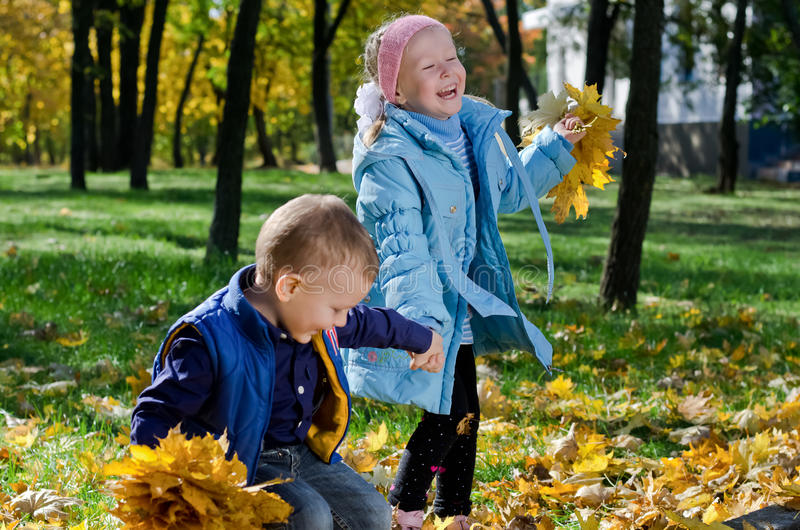 Laughing children playing with fall leaves royalty free stock photography