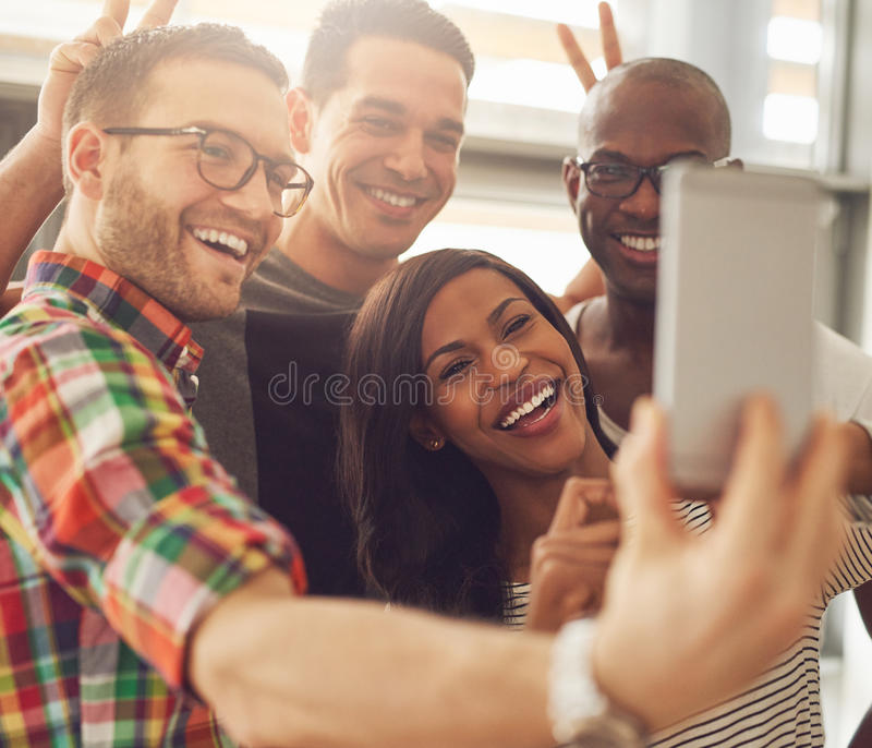 Laughing co-workers taking self portrait. Group of four diverse cheerful co-workers taking self portrait and making funny gestures with hands at small office in royalty free stock photography