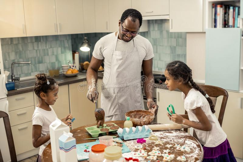 Friendly family laughing while cooking cupcakes together. Laughing and cooking. Friendly happy family laughing while cooking cupcakes together stock image
