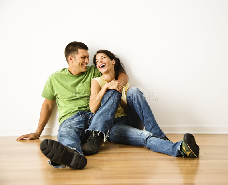 Laughing couple. Attractive young adult couple sitting close on hardwood floor in home smiling and laughing royalty free stock photo