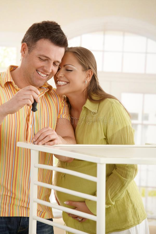 Laughing couple with baby bed royalty free stock image