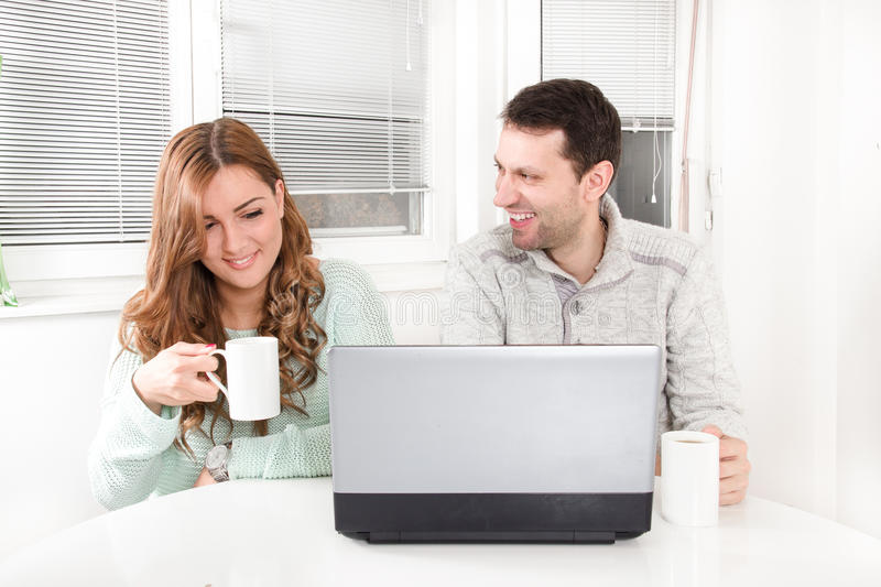 Laughing couple browsing the internet at the laptop. At home with a cup in hands drinking tea or coffee royalty free stock photography