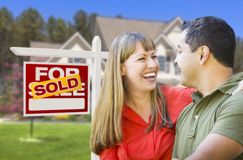 Laughing Couple in Front of Sold Real Estate Sign and House. Happy Mixed Race Couple in Front of Sold Home For Sale Real Estate Sign and House royalty free stock image