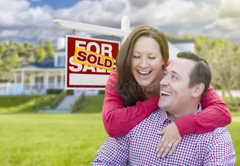 Laughing Couple In Front of Sold For Sale Sign and House. Happy Laughing Couple In Front of Sold For Sale Real Estate Sign and Beautiful House stock photography