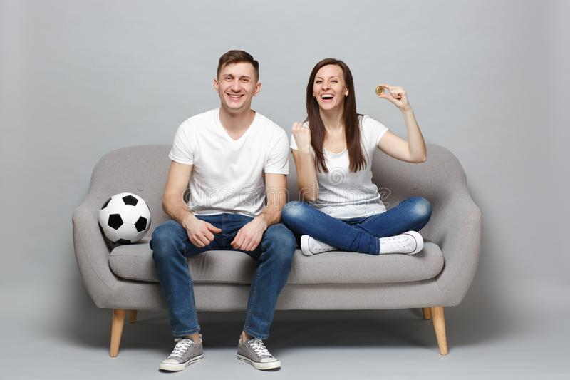 Laughing couple woman man football fans cheer up support favorite team holding bitcoin, future currency, doing winner stock photo