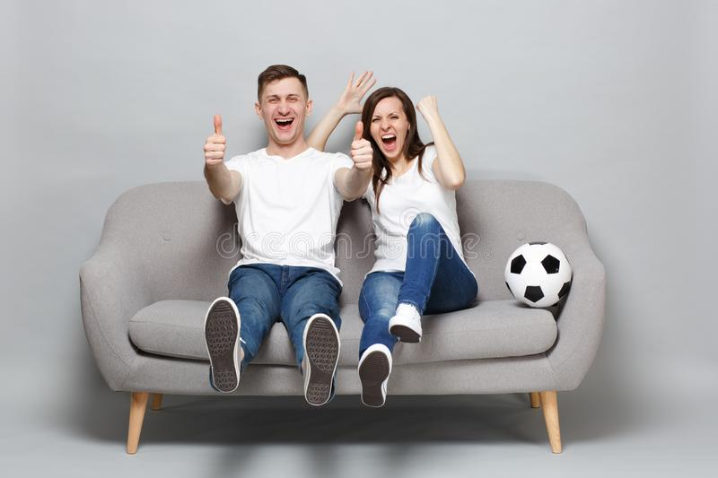 Laughing couple woman man football fans cheer up support favorite team with soccer ball, showing thumbs up, clenching stock photography