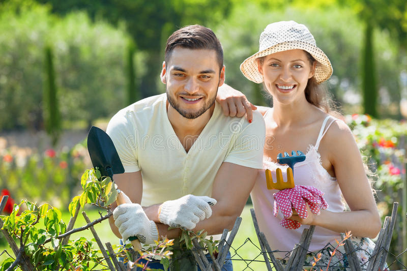 Laughing couple working in garden. Laughing couple working in the flower garden royalty free stock images