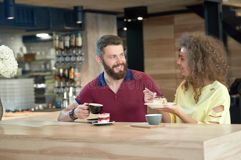 Laughing couple of young students drinking coffee, eating cakes in cafe. stock photo
