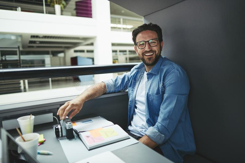 Laughing designer working inside of an office meeting pod stock photography