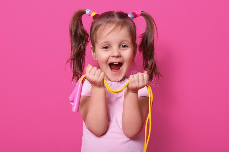 Laughing cute girl wears rose t hirt, stands isolated over pink background, hold bright skipping rope in hands. Happy child with stock photography