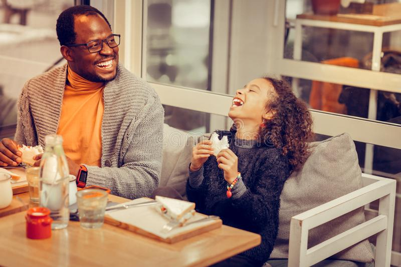 Curly dark-haired daughter laughing while having lunch with father. Laughing daughter. Curly dark-haired beautiful daughter laughing while having lunch with royalty free stock photos