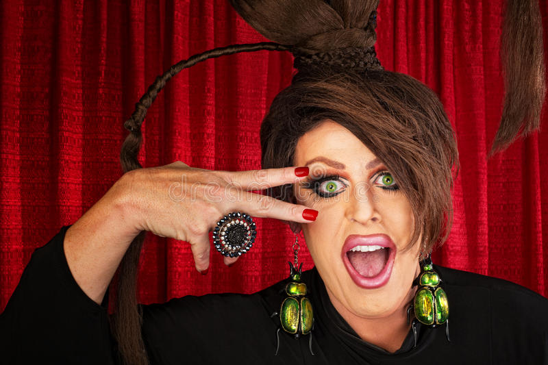 Laughing Drag Queen. Laughing Caucasian drag queen in theater with hand near face stock photos