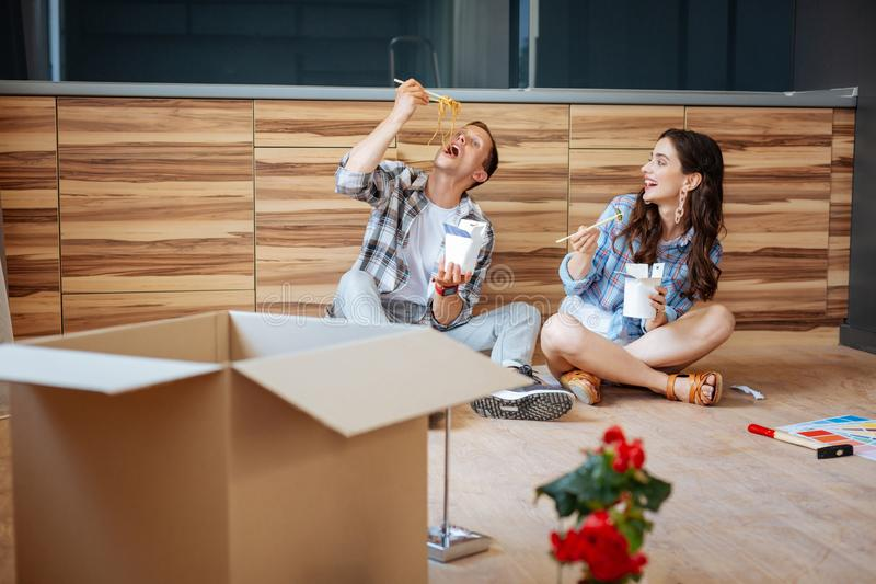 Couple laughing and eating yummy noodles in new flat royalty free stock images