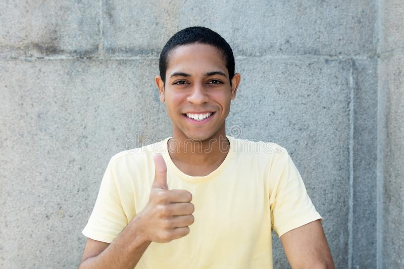 Laughing egyptian young adult man showing thumb up royalty free stock image