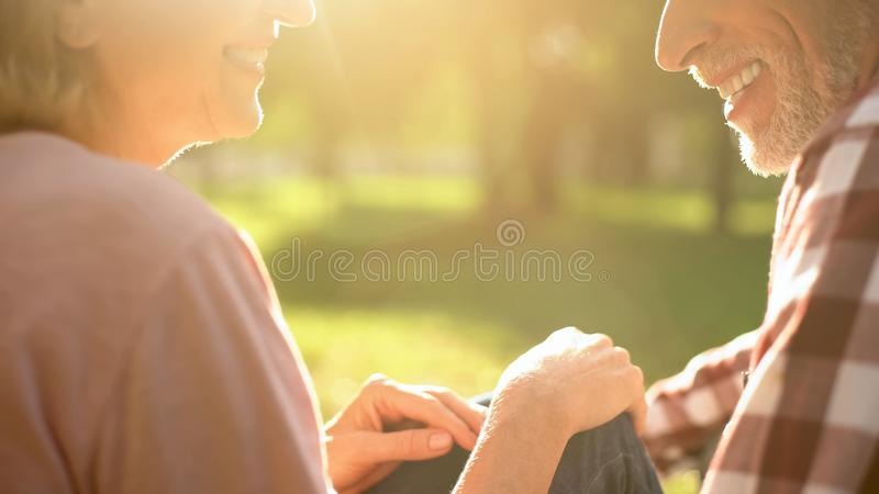 Laughing elderly couple relaxing in park, talking about love and enjoying date stock images