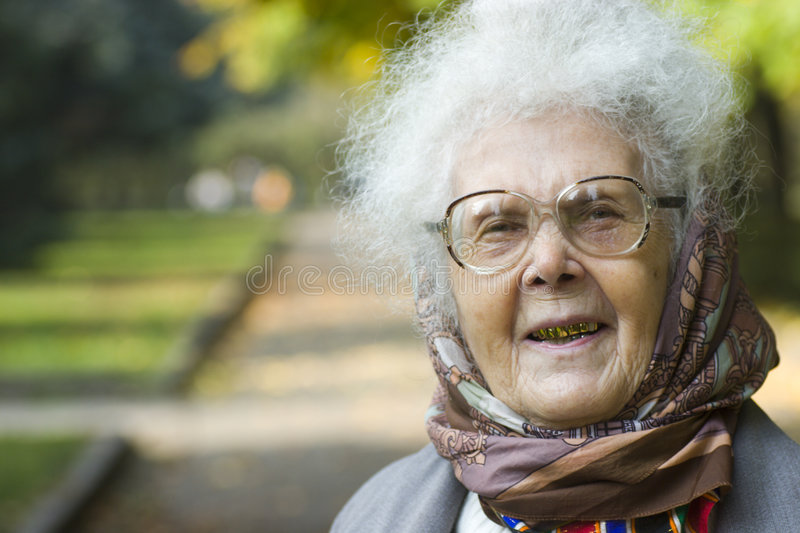 Laughing elderly woman in park royalty free stock images