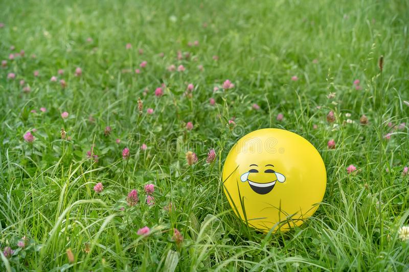 Laughing emoji face on a yellow balloon laying on the grass royalty free stock images