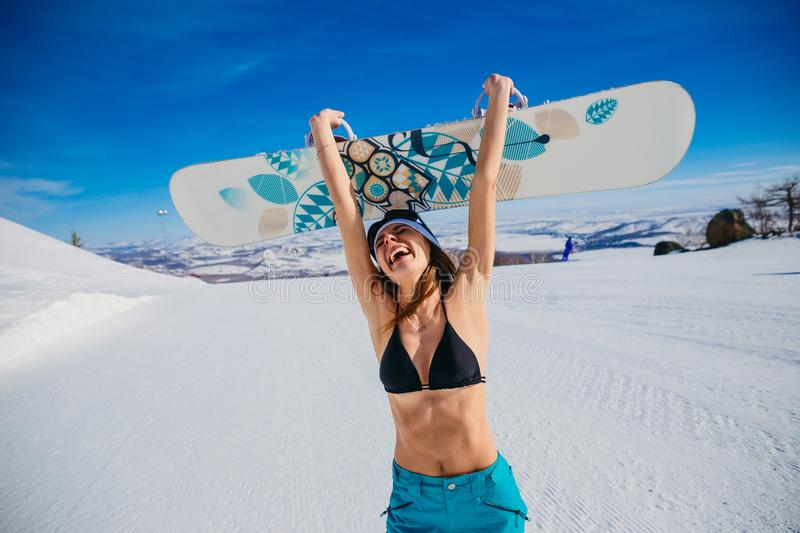 Laughing emotional young woman in a swimsuit and hat holding a snowboard in her hands in winter. Extreme. Euphoria. Cheerful stock photo