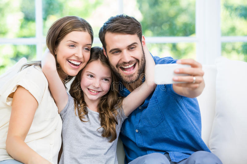 Laughing family clicking selfie with smartphone royalty free stock photography