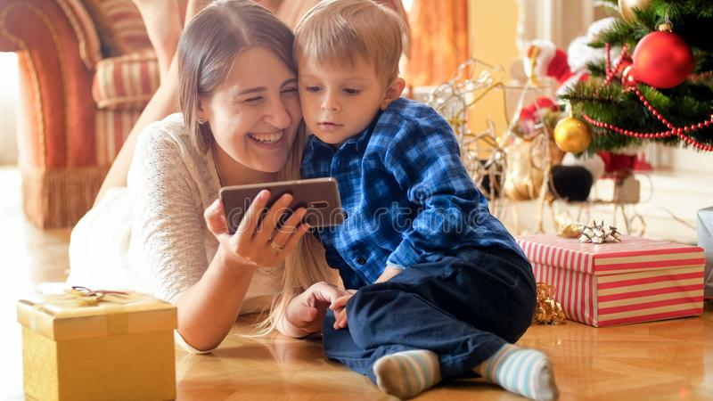 Laughing young family with little son lying on floor on Christmas morning and watching video on smart phone stock photos