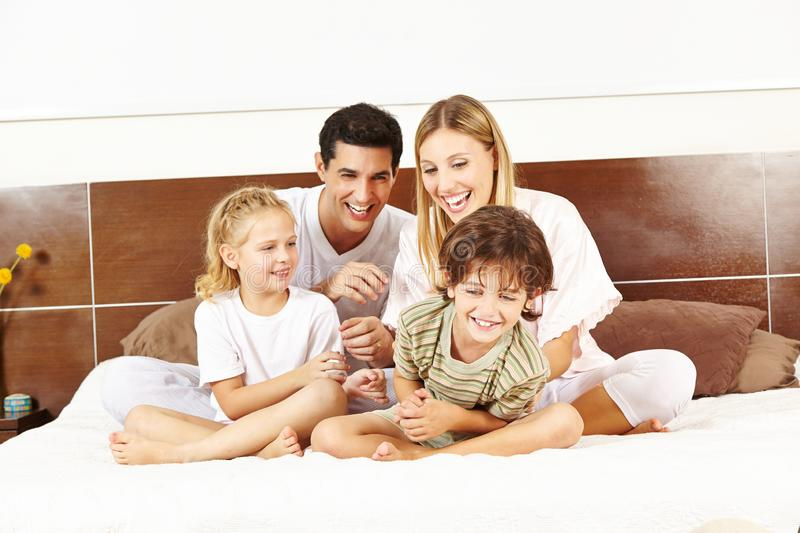 Laughing family is sitting in bed stock photography
