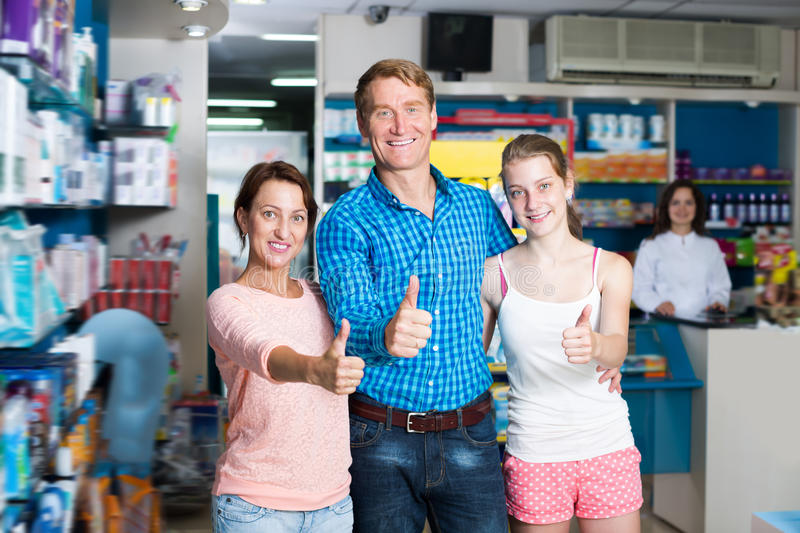 Laughing family of three holding thumbs up stock images