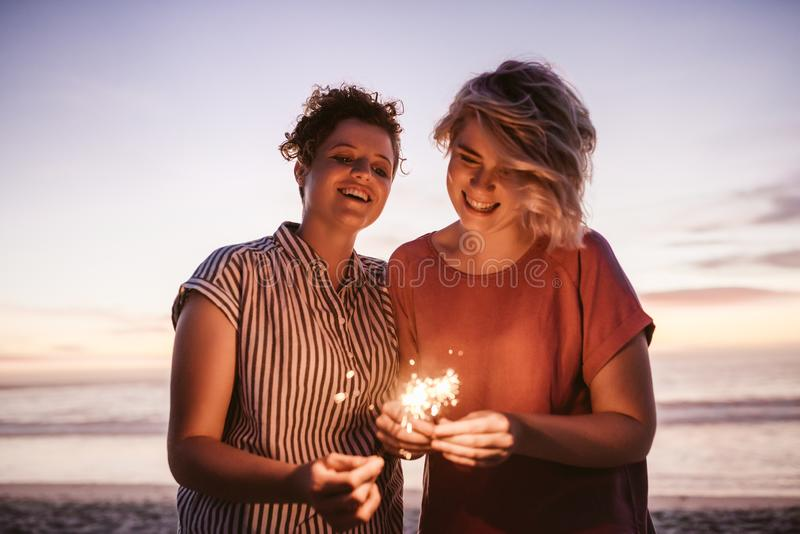 Laughing female friends playing with sparklers during a beach sunset royalty free stock image