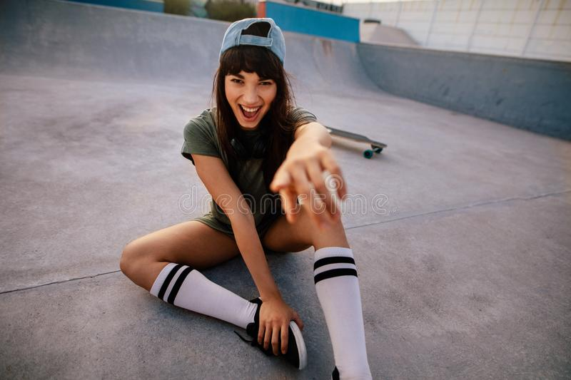 Laughing female skateboarder pointing at camera. Laughing young female skateboarder sitting at skate park and pointing at camera. Cheerful woman outdoors at stock photos