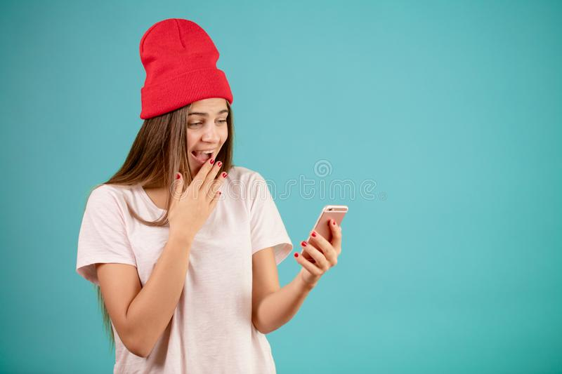 Laughing female student in white T-shirt and red cap royalty free stock photos