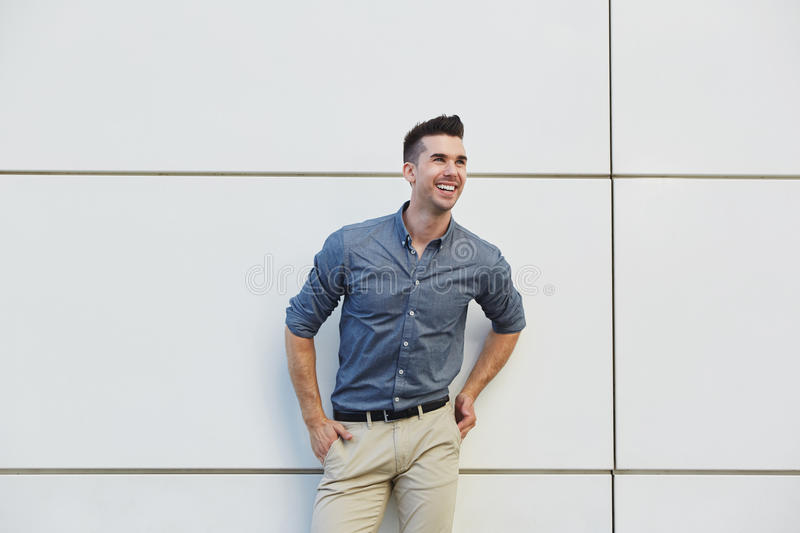 Laughing friendly business man standing by white wall royalty free stock photos