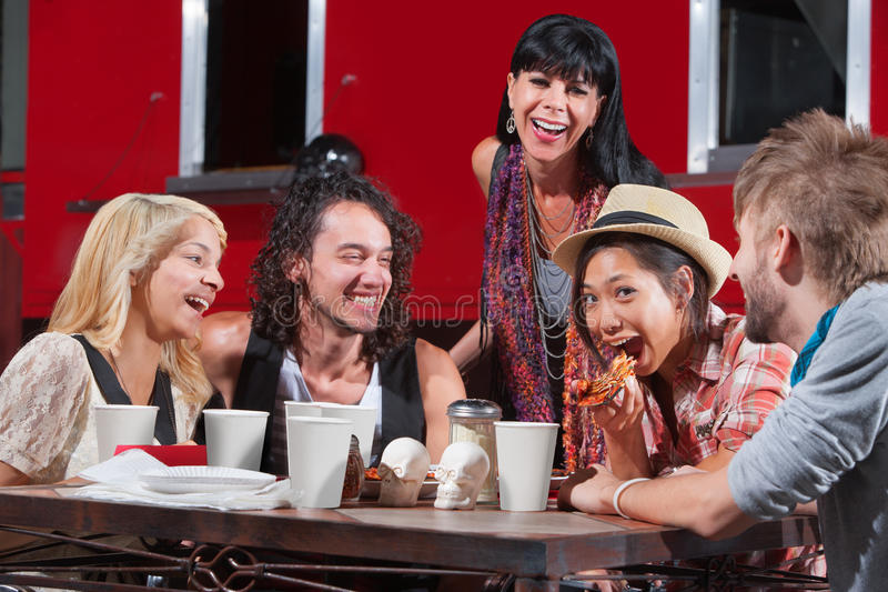 Laughing Friends Eating Pizza Stock Images
