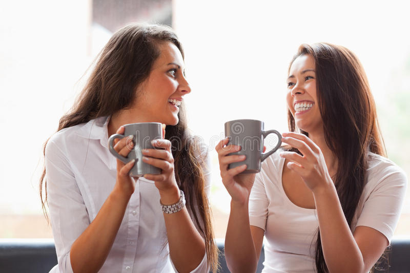 Laughing friends having a coffee royalty free stock photos