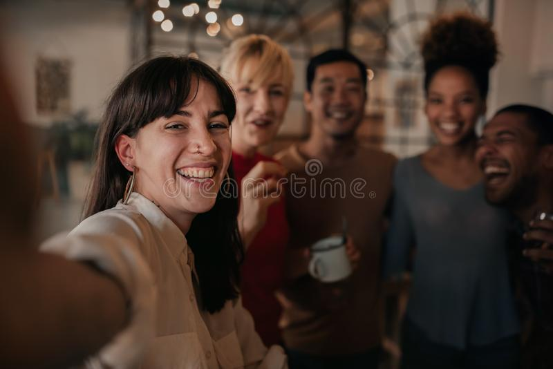 Laughing friends taking selfies together in a bar at night royalty free stock photo