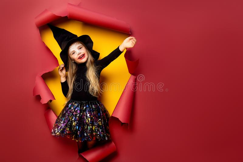 Laughing funny child girl in a witch costume in halloween royalty free stock photos