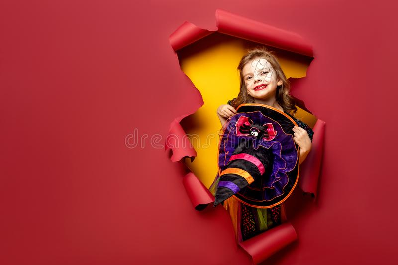 Laughing funny child girl in a witch costume in halloween royalty free stock photography