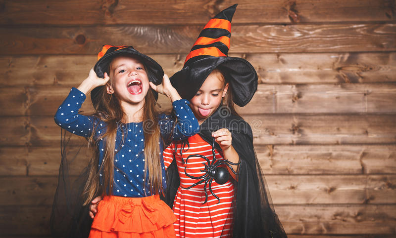 Funny children sister twins girl in witch costume in halloween. Laughing funny children sister twins girl in a witch costume in halloween stock images