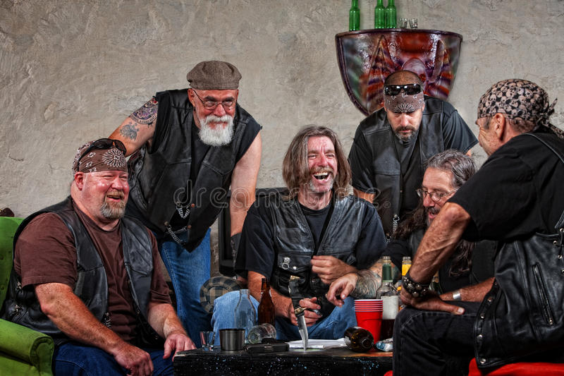 Laughing Gang Members. Six male biker gang members laughing with weapons on table royalty free stock photos